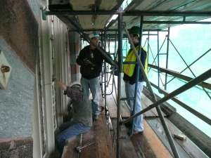 On the scaffold, behind the curtain, preparing to remove the stained glass panels.  Photo, the author.