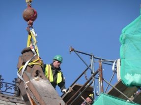 Lifting the capstone off the east gable, the first stone removedd